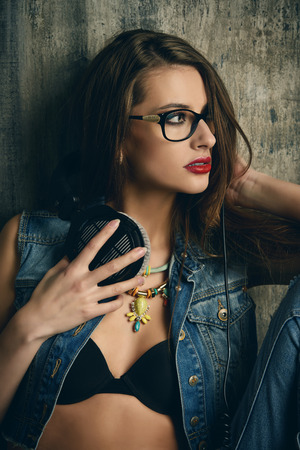 Modern girl in casual jeans clothes listens to music in headphones. Fashion. Stock Photo