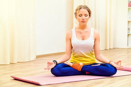 meditation room: Beautiful athletic girl doing yoga exercises indoor. Lotus pose. Meditation. Stock Photo