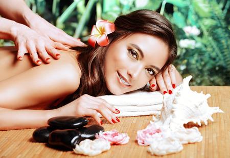 La terapia manual. Mujer joven hermosa que consigue masaje en un salón del balneario. Salud, cuidado del cuerpo.