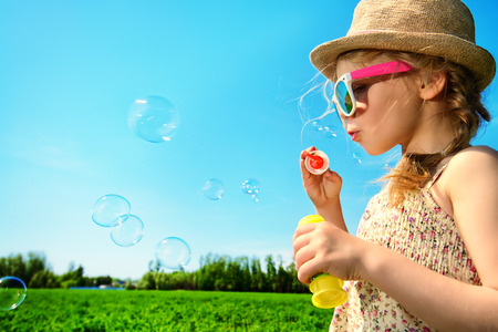 childhood: Pretty little girl blows bubbles on a meadow in summer day. Happy childhood. Blue sky.