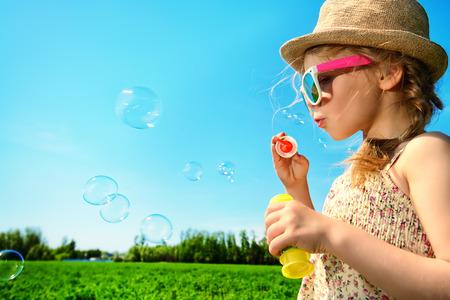 meadow: Pretty little girl blows bubbles on a meadow in summer day. Happy childhood. Blue sky.