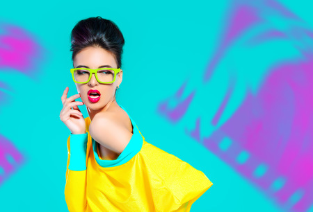 celadon blue: Expressive fashion model posing in vivid colourful clothes. Bright fashion. Optics, eyewear. Studio shot.