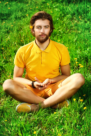 Handsome young man sitting on a grass and doing yoga exercises. photo