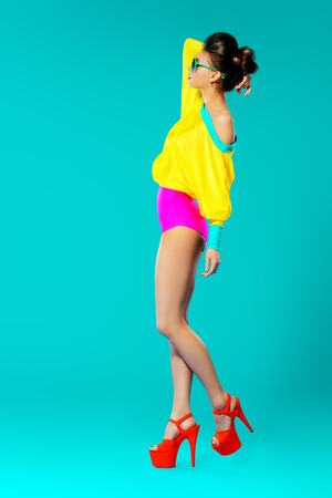 eyewear fashion: Expressive fashion model posing in vivid colourful clothes. Bright fashion. Optics, eyewear. Studio shot.