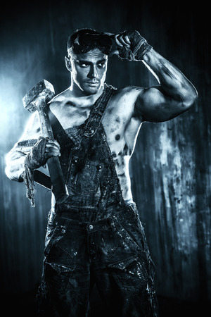 coal miner: Handsome muscular coal miner with a hammer over dark grunge background. Mining industry. Art concept.