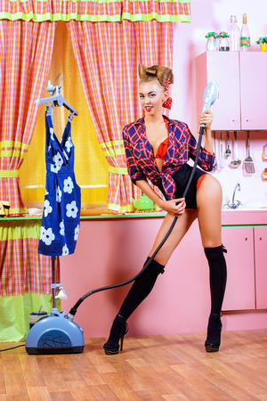 Charming pin-up girl ironing her dress and singing on a glamorous pink kitchen. Retro style. Fashion. photo