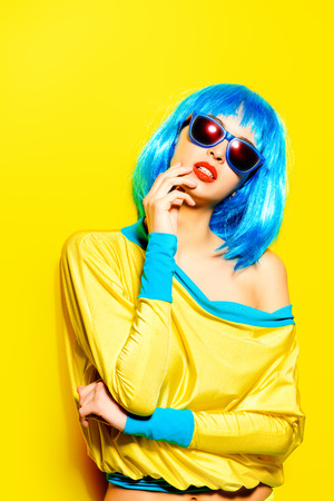 Bright glamorous girl in vivid clothes and a wig alluring over yellow background. Beauty, fashion. Cosmetics, hairtsyle. Optics, eyewear. photo