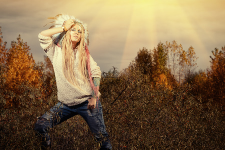 ceremonial clothing: Beautiful girl in style of the American Indians dancing in the rays of the autumn sun. Western style. Jeans fashion.