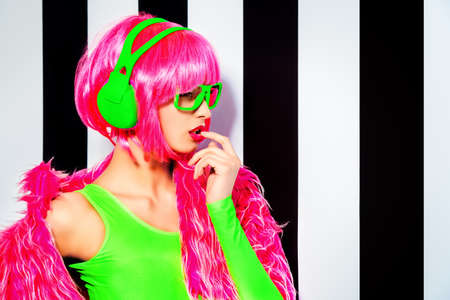 Trendy DJ girl in bright colorful clothes and headphones posing over black-and-white stripes. Party style. Fashion studio shot. photo