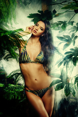 bronzed: Beautiful sexy woman in bikini among tropical plants. Beauty, fashion. Spa, healthcare. Tropical vacation.