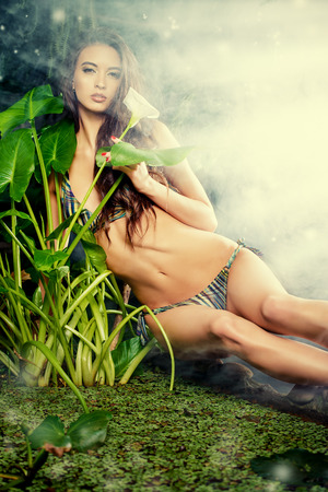 Beautiful slim girl sitting by the pond in the rainforest. Beauty, fashion. Spa, healthcare. Tropical vacation. photo