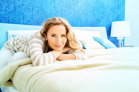 Happy elegant woman having a rest in her bedroom. Home interior, furniture. Lifestyle. photo