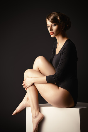 tight body: Art portrait of a beautiful slim model in black fitting clothing. Beauty, fashion. Body care.