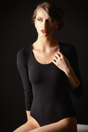 tight fitting: Slender woman in black fitting body over black background. Beauty, fashion. Body care.