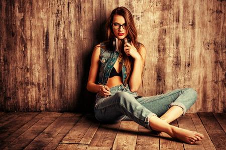 donne eleganti: Pretty girl in jeans casuali vestiti seduto su un pavimento di legno vicino al muro grunge. Fashion. Archivio Fotografico