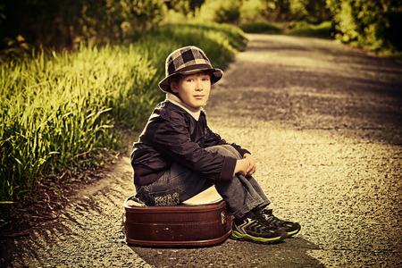 street kid: Portrait of a cute dreamy boy sitting on the old suitcase outdoor. Summer day. Adventure.
