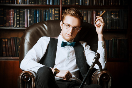 Elegant young man in a suit sitting in armchair and smoking a cigar. Vintage room. Fashion. photo