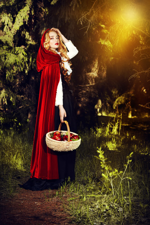 Beautiful blonde woman in  old-fashioned dress and red cloak walking throgh the forest with a basket of apples. Stock Photo