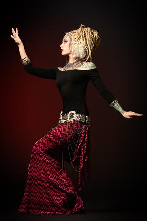BELLY DANCING: Studio shot of a beautiful traditional female dancer. Ethnic dance. Belly dancing. Tribal dancing.