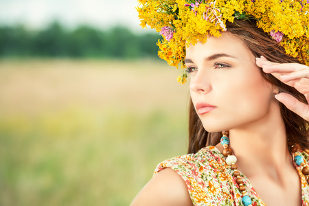 meadows: Romantic girl in a wreath of wild flowers in a field. Summer life. Beauty.
