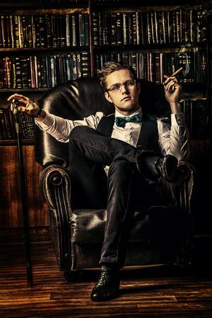hombre fumando puro: Hombre joven elegante con un traje sentado en el sillón y fumando un cigarro. Sitio de la vendimia. La Moda.
