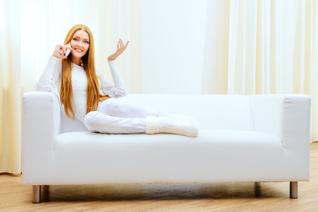 rest day: Beautiful young woman talking on the phone at home sitting on the couch. Stock Photo