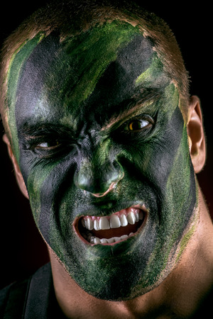 formidable: Close-up portrait of a furious soldier in war paint. Black background. Military, war. Special forces. Stock Photo