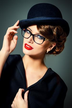 bowler hat: Beautiful woman wearing glasses and bowler hat. Retro style. Beauty, fashion. Make-up. Optics, eyewear. Stock Photo