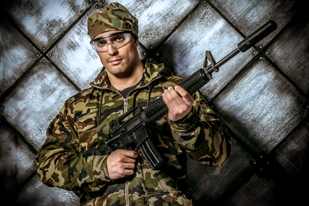 Brave soldier in camouflage holding automatic rifle. Military. photo