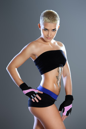 athletic: Portrait of a professional athlete woman bodybuilder with a perfect athletic physique. Fitness sports. Healthcare, bodycare. Martial arts, fighter.