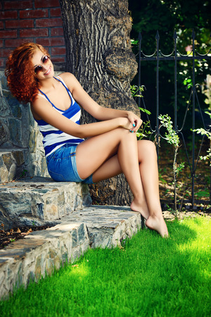 foxy: Beautiful young woman with curly foxy hair outdoors. Beauty, fashion.