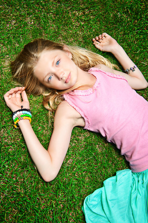 Beautiful smiling girl lying on a green lawn in the park. Sunny summer day. photo