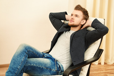 comfortable chair: Dreamily thoughtful young man sitting relaxed on the armchair. Stock Photo