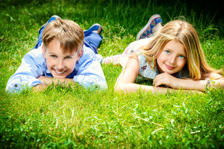 two generation family: Two cheerful teenagers on the grass in the park. Summer. Friendship.