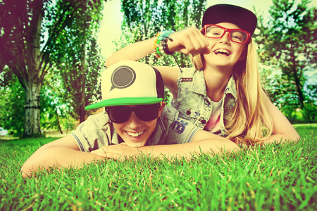 Two cheerful teenagers on the grass in the park. Summer. Friendship. photo