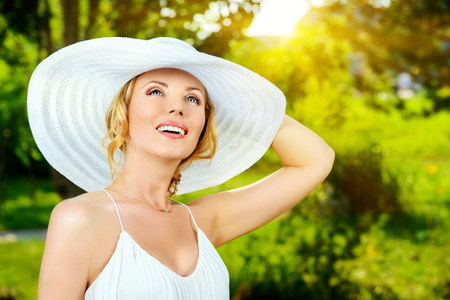 Portrait of a beautiful elegant woman in light white dress and hat standing in the summer park. Beauty, fashion. photo