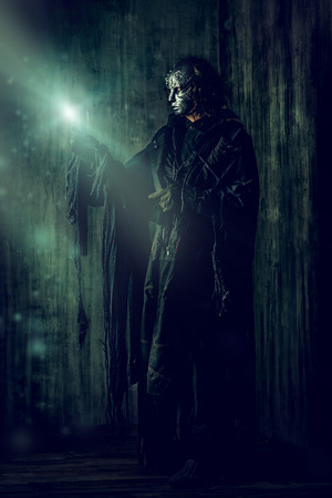 scary man: Scary man in iron mask and black robe. Fantasy. Halloween.