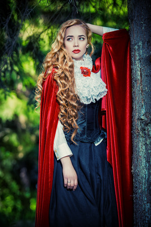 Beautiful blonde woman in  old-fashioned dress and red cloak in a fairy forest. photo