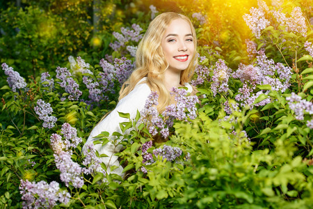 Lovely young woman with magnificent blonde hair near blooming lilac. Countryside. Stock Photo