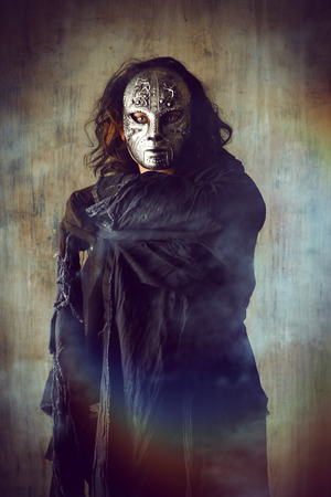 robes: Scary man in iron mask and black robe. Fantasy. Halloween.