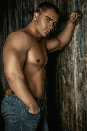 manly man: Portrait of a handsome muscular man full of strength standing by a grunge wall.