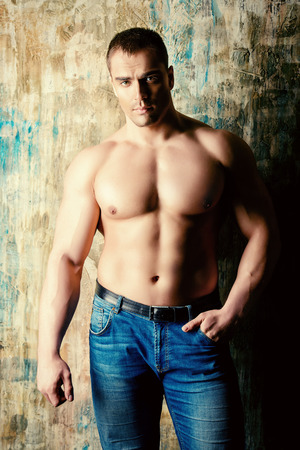 manly man: Portrait of a handsome muscular man full of strength standing by a grunge wall. Jeans style.