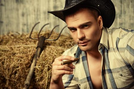 hombre fumando puro: Vaquero atractivo fumando un cigarro. Estilo occidental. Pantalones de mezclilla de moda.