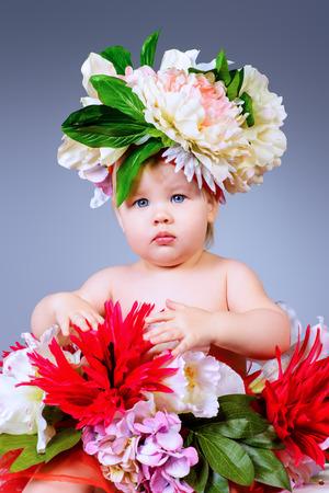Sweet little baby girl sitting among flowers. Beauty, childhood. Healthcare. photo