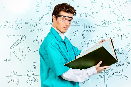 conducting: Young scientist conducting research, making experiments and writes the results. Stock Photo
