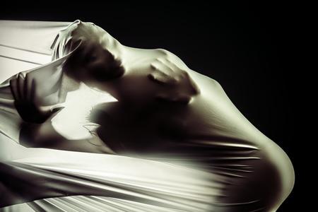 danza moderna: Silueta femenina romper a través de la tela blanca sobre fondo negro. Proyecto de arte, teatro. La danza moderna. Foto de archivo