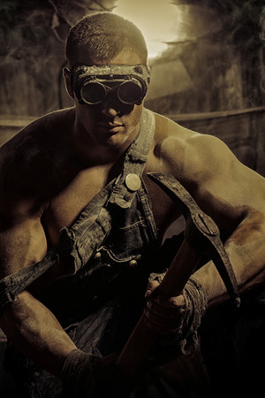 masculine: Masculine dirty coal miner with a pickaxe over dark grunge background. Mining industry. Strength. Bodybuilding.
