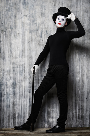 dramatic characters: Full length portrait of an elegant male mime artist standing with walking stick by a grunge wall.