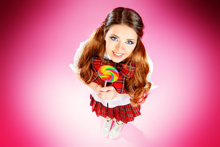 checkered skirt: Pretty smiling teen girl in school plaid skirt and white blouse posing with lollipop over pink background. Anime style.