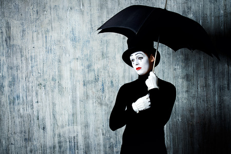 comedy: Portrait of a male mime artist standing under umbrella expressing sadness and loneliness. Grunge background. Stock Photo